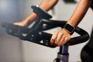 woman gym doing spinning cyclo indoor with smart watch 1139 1716